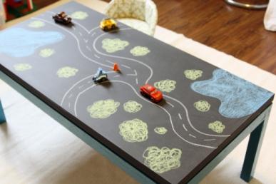 Tem uma mesinha sem uso? Uma camada de tinta de lousa transforma a mesa em uma super pista de carrinhos!